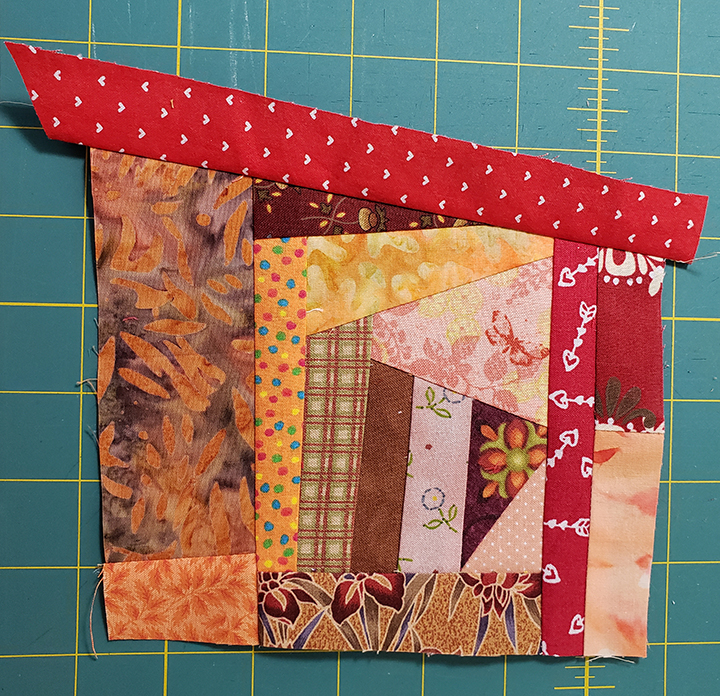 Sample Crumb Block made with red and orang fabric. From my article Quilts from Crumbs